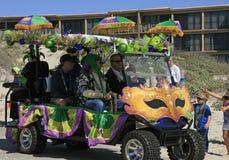 Maskeringar, gräsplan, guld och lilor dekorerar en golfvagn på den barfota Mardi Gras Parade Royaltyfri Bild