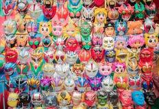 Maskeringar hänger i ett bås på den Amarin tempelfestivalen i Bangkok Arkivbilder