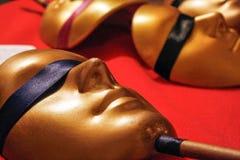 Maskeringar som en framsida som ligger på tabellen som täckas av den röda torkduken Royaltyfri Fotografi