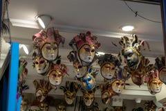 Maskeringarna av den Venedig karnevalet hängde i shoppar royaltyfri foto
