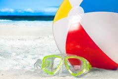 Maskeringsskyddsglasögon och färg klumpa ihop sig på en sand på strandbakgrund Royaltyfri Foto