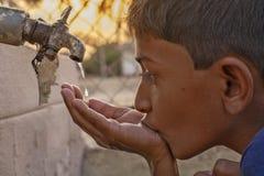 Maski,卡纳塔克邦,印度- 26,2019年3月:儿童饮用水特写镜头直接地从公司自来水在印度 免版税库存照片