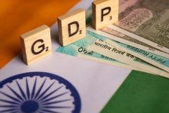 Maski, Índia 13, em abril de 2019: GDP ou produtos internos brutos em letras de bloco de madeira na bandeira de Indina com moeda imagens de stock royalty free