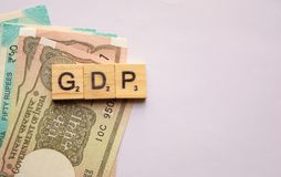 Maski,India 13,April 2019 : GDP or gross domestic product in wooden block letters with Indian currency on isolated. Background royalty free stock photography