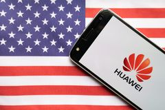 Maski, India - June 21, 2019: Huawei logo on screen of Mobile on US flag.  royalty free stock photo