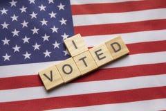Maski, Indien 26, im April 2019: Ich wählte Holzklotzblockschrift, US-Wahlen auf amerikanischer Flagge lizenzfreie stockfotos
