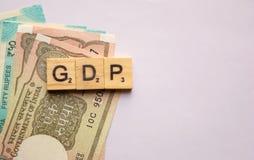 Maski, la India 13, abril de 2019: GDP o producto interno bruto en letras de molde de madera con moneda india en aislado fotografía de archivo libre de regalías