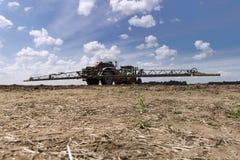 Maskin för att bespruta bekämpningsmedel och växtbekämpningsmedel i fältet mot blå himmel Tungt maskineri för jordbruk royaltyfria foton