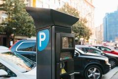 Maskin för att betala parkering Närbild - maskin för att betala parkering på bakgrund av oskarpa bilar Arkivfoto