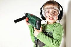 Maskin för borrande för pojkeinnehavgräsplan på hans skuldra arkivfoton