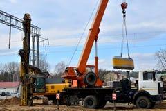 Maskin för fundamenthögborrande och mobil kran på konstruktionsplatsen arkivfoto