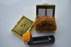 Maskin för fyllnads- cigaretter på tabellen med det gula locket och någon tobak i den och en snuffbox med tobak i den Arkivbild