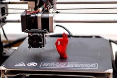 maskin för printing 3d och utskrivavet objekt utskrivavet gömma i handflatan rött arkivfoto