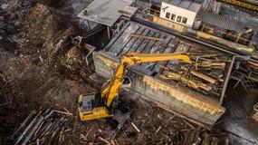 Maskinen lyfter bråte på en wood fabrik Sikt för öga för fågel` s arkivfoton