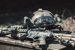 Maskinen, maskingevär, arméhjälm med en ficklampa som ligger i en hög på en träask av ammunitionar Royaltyfri Bild