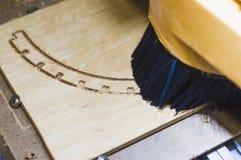 Maskinen snider trät av de lockiga styckena av kryssfaner Arkivfoto