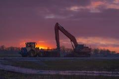 Maskiner för tungt arbete på solnedgången fotografering för bildbyråer