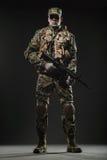 Maskingevär för soldatmanhåll på en mörk bakgrund Royaltyfri Bild