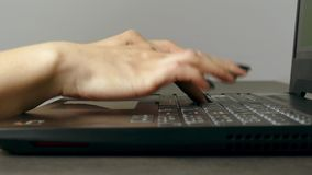 Maskinskrivning för den unga kvinnan fastar på bärbar datortangentbordet stock video