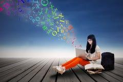 Maskinskrivning för kvinnlig student på en utomhus- bärbar dator Arkivbilder