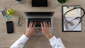 Maskinskrivning för medicinsk arbetare på bärbara datorn som håller elektroniska sjukdomshistorier, bästa sikt arkivfoto