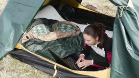 Maskinskrivning för ung dam på bärbara datorn som ligger i tältet arkivfilmer