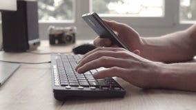 Maskinskrivning för ung man på ett tangentbord och använda mobiltelefonsmartphonen och skriva därefter en messege Freelancerfotog lager videofilmer