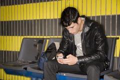 Maskinskrivning för ung man på det väntande på gångtunneldrevet för smartphone Royaltyfria Foton