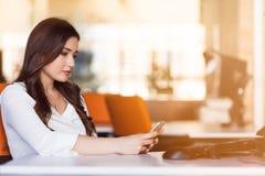 Maskinskrivningaffärsmeddelande Säker ung kvinna i smart telefon för smart innehav för tillfälliga kläder och se den med leende Royaltyfri Fotografi