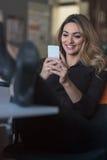 Maskinskrivningaffärsmeddelande Säker ung kvinna i smart telefon för smart innehav för tillfälliga kläder och se den med leende Royaltyfri Foto