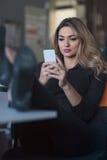 Maskinskrivningaffärsmeddelande Säker ung kvinna i smart telefon för smart innehav för tillfälliga kläder och se den med leende Arkivbild