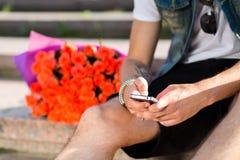 Maskinskrivningmeddelande för ung man i mobiltelefonen på trappa Royaltyfri Foto