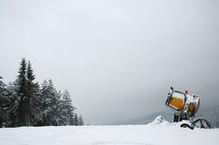 maskinställeskidåkning som snowmaking Arkivbild