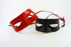 Masks. Two leather Lone Ranger type masks, red and black, isolated against a white background