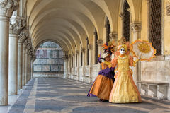 Masks in Beautiful female costumes under arcades of Doge´s palace at Carnival in Venice, Italy Stock Image