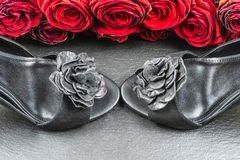 High heel shoes,roses on black stone background royalty free stock photography
