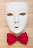 Masks and bow ties on the wood. En background Royalty Free Stock Images