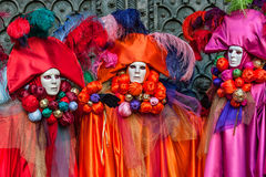 Masks in multicolored costumes at carnival in Venice Stock Image