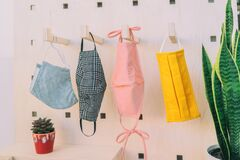Free Masks Of Many Colors For Corona Virus Prevention Hanging On Wall At Home Or Store. Pastel Color For Cute Face Mask Stock Image - 194758741