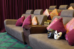 Masks on soft couch with cushions in movie theater. Stock Image