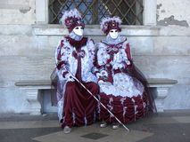 Masks with walking stick, Carnival of Venice. Couple of masks in red-wine outfit sitting on a little bench, with a walking stick, Carnival of Venice Royalty Free Stock Photo