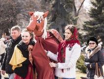 Maslenitsa-女孩跳舞与一匹装饰马在公园为 免版税图库摄影