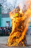 Maslenitsa celebration. Large scarecrow burns on the stage of the city park as a tradition of farewell to winter stock photos