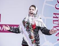 Maslenitsa-the dziewczyna w krajowym szaliku śpiewa przy festiwalem Zdjęcia Royalty Free