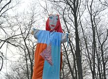 Maslenitsa effigy with the drawn person against the background of trees.  royalty free stock images