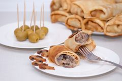 Maslenitsa. Pancake rolls or French stuffed crepes with mushrooms. And olives stock photo