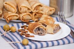 Maslenitsa. Pancake rolls or French stuffed crepes with mushrooms. And olives stock photography