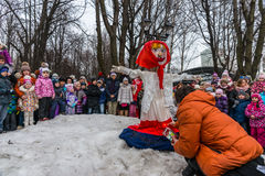 Maslenitsa (pancake week). Man sets fire to an effigy of Winter, around which there are people. Stock Images