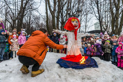 Maslenitsa (pancake week). Man sets fire to an effigy of Winter, around which there are people. Royalty Free Stock Photo