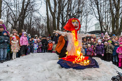 Maslenitsa (pancake week). Man sets fire to an effigy of Winter, around which there are people. Winter 2015. Day. Russia. Moscow. Maslenitsa (pancake week). Man royalty free stock image